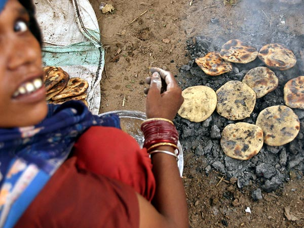 A woman cooks bread over burning cow dung in New Delhi, India